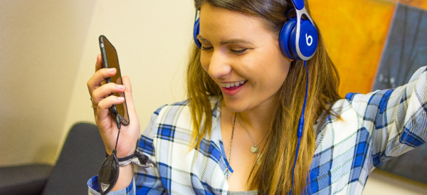 Woman in blue plaid shirt headphones with SoundBrake 600x274